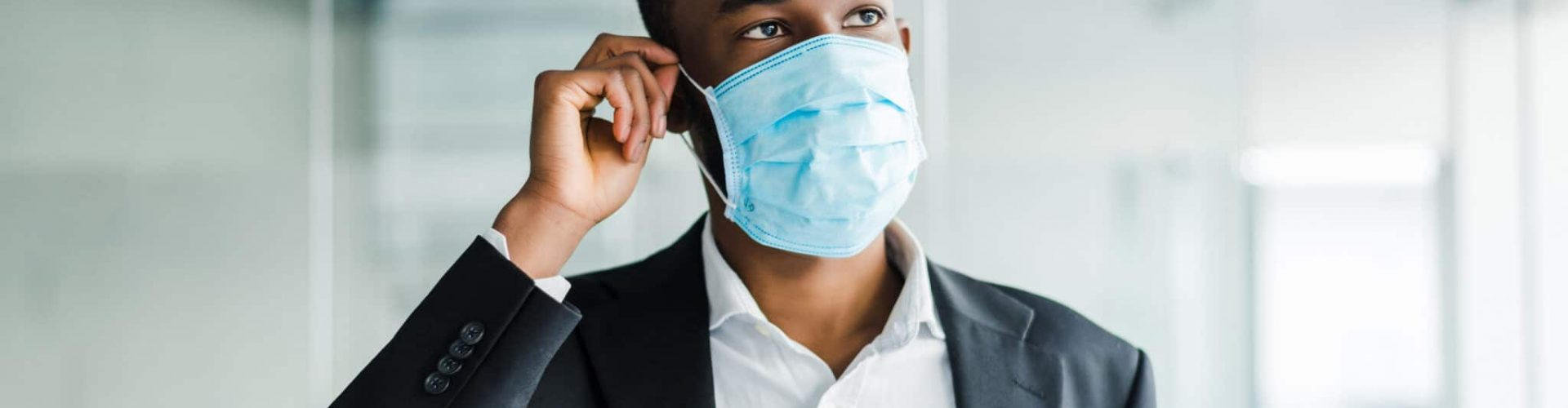 African young business man wearing a mouth protection to prevent getting sick at work in office